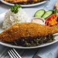 side-view-chicken-cutlet-crispy-panco-chicken-breast-with-rice-garnish-cucumber-tomato-carrot-and-sauce-on-a-plate
